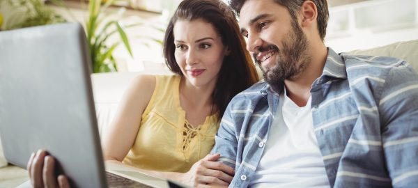 Happy couple shopping online on bed in living room at home
